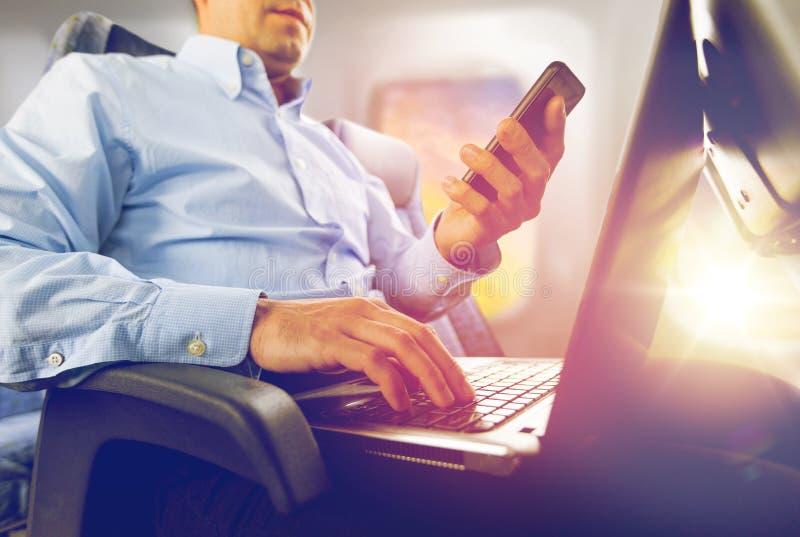 Бизнесмен с smartphone и компьтер-книжкой в плоскости  стоковые изображения