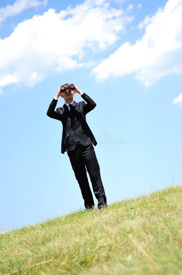 Бизнесмен с spyglass стоковое изображение