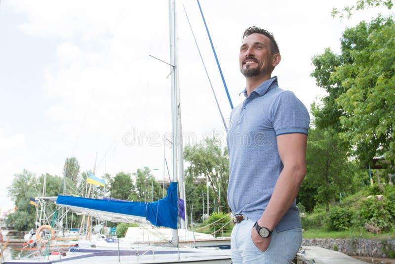 Бизнесмен тратя время идя на Марине и смотря sightseeing на каникулах Портрет молодого счастливого яхтсмена стоковые изображения