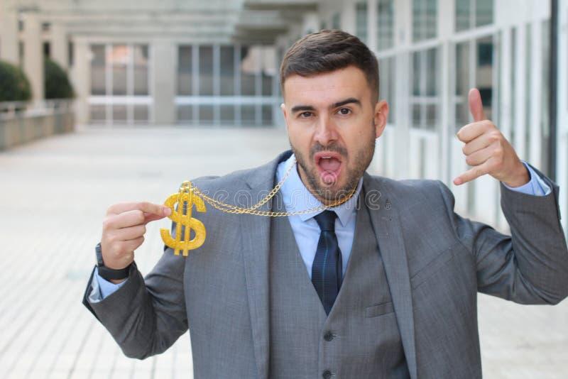 Бизнесмен тряся золотое ожерелье с знаком доллара стоковые фото