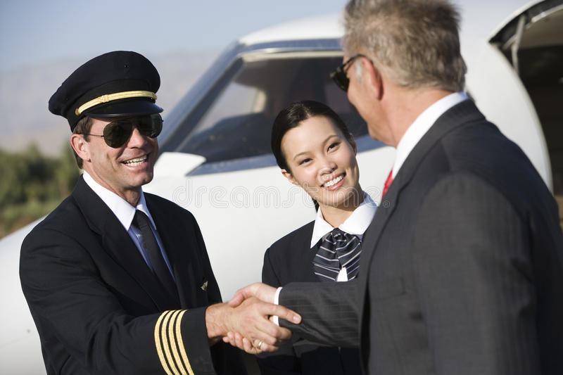 Бизнесмен тряся руки с капитаном самолета стоковые фото