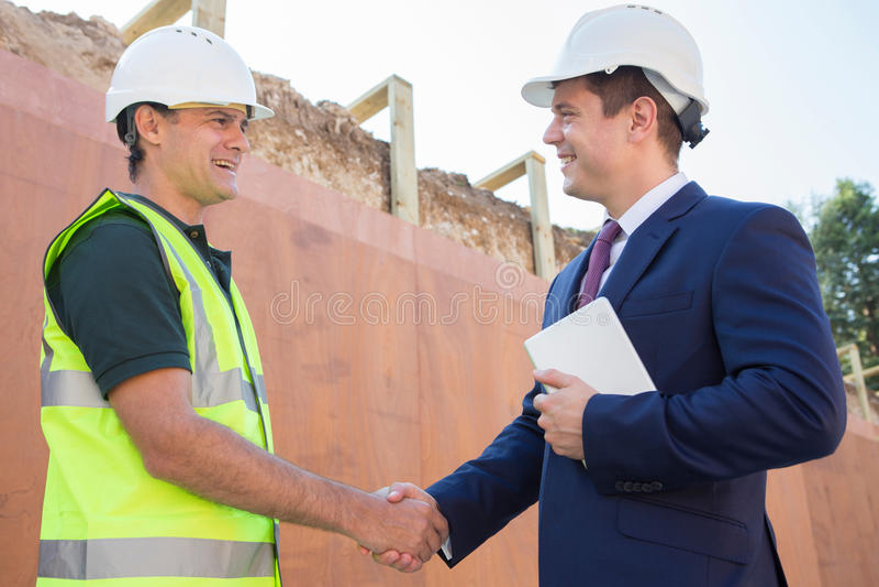Бизнесмен тряся руки с построителем на строительной площадке стоковое фото rf