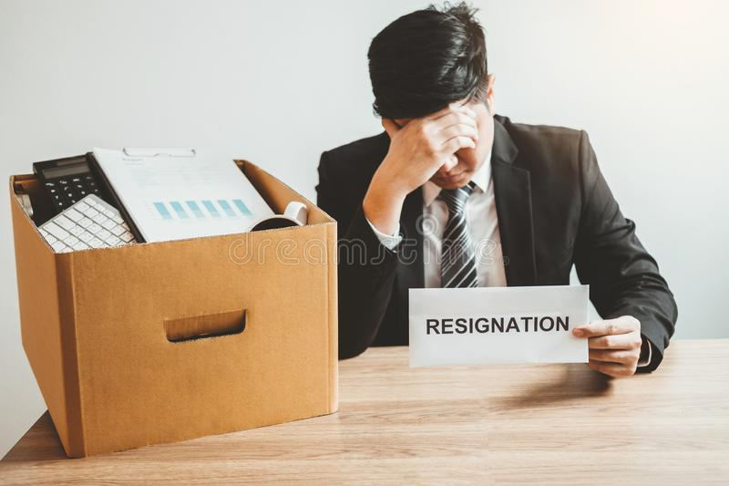 Бизнесмен усиливая с уведомлением об отставке для прекращенный работе пакуя коробку и покидая офис, концепция безропотности стоковые изображения rf