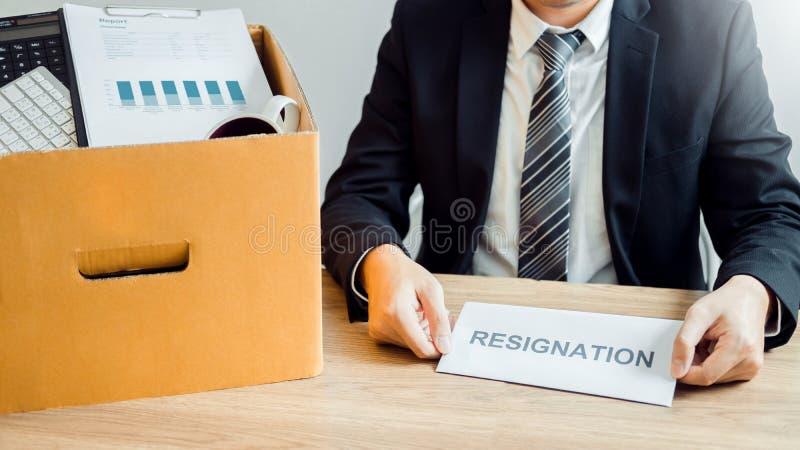 Бизнесмен усиливая с уведомлением об отставке для прекращенный работе пакуя коробку и покидая офис, концепция безропотности стоковые изображения