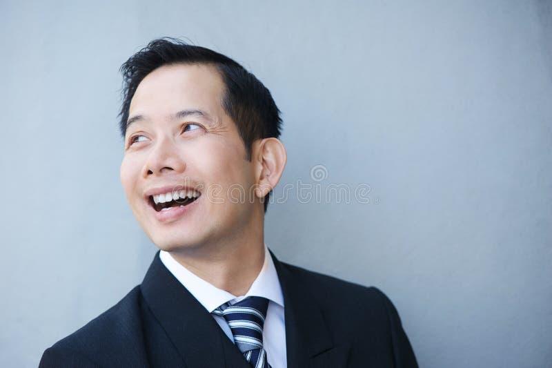 Download Бизнесмен усмехаясь на серой предпосылке Стоковое Фото - изображение насчитывающей современно, смотреть: 41653542