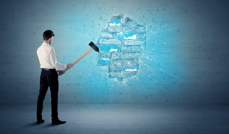 Бизнесмен ударяя кирпичную стену с огромным молотком стоковое фото