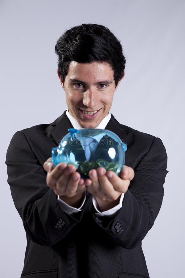 бизнесмен чеканит полное piggybank удерживания стоковое фото rf