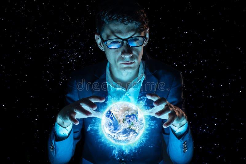 Бизнесмен человека держа руки над голубой накаляя сферой в форме земли планеты Элементы обеспечили NASA стоковое изображение rf
