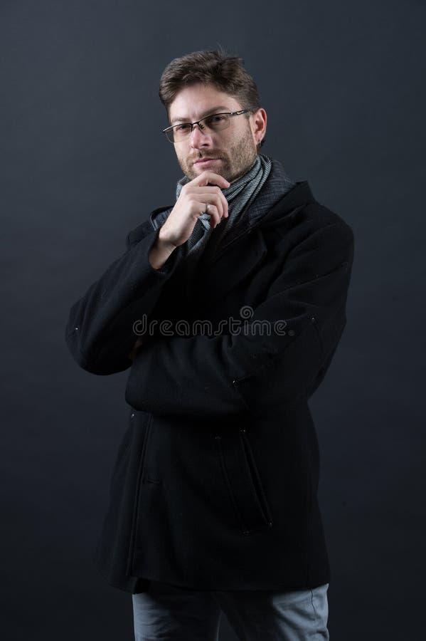 Бизнесмен человека думает в стеклах на бородатой стороне в пальто стоковые изображения