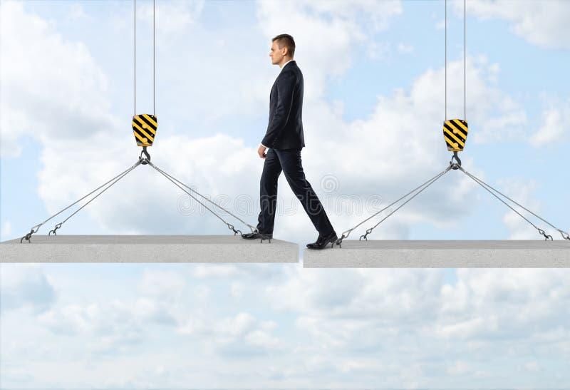 Бизнесмен шагает над зазором от одной конкретной панели к другим в воздухе на предпосылке неба стоковое изображение