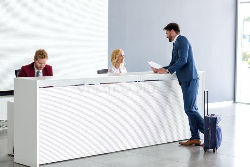 Бизнесмен flirting на приеме с женским работник службы рисепшн стоковое фото