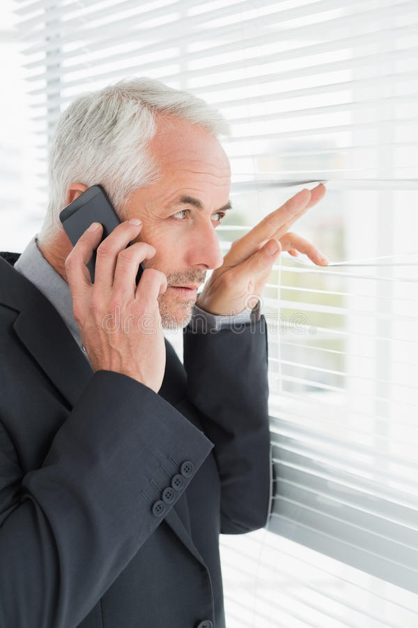 Бизнесмен peeking через шторки пока на звонке в офисе стоковое изображение rf