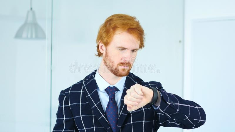 Бизнесмен Redhead ждать на работе, наблюдая времени на вахте стоковые изображения rf