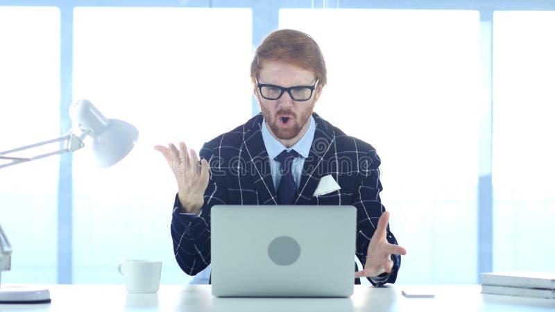 Бизнесмен Redhead сердитый на работе, реагируя к потере стоковая фотография