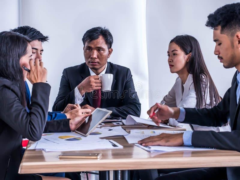 Бизнес-группы предлагают планы организационной деятельности к инвесторам через планшеты стоковое фото rf