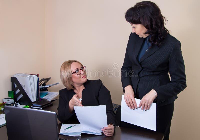 Бизнес-леди давая отчет к боссу стоковые фото