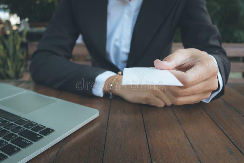 Бизнес-леди дает визитную карточку для тона темноты клиента стоковое изображение rf