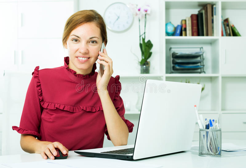 Бизнес-леди беседуя на телефоне и используя компьютер стоковые фотографии rf