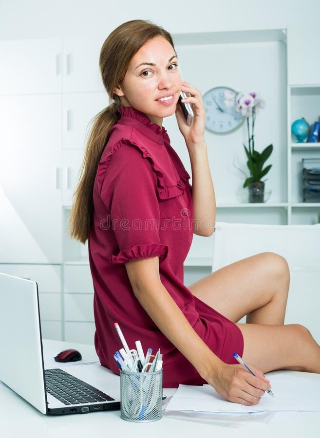Бизнес-леди беседуя на телефоне пока сидящ на работая столе a стоковые фото