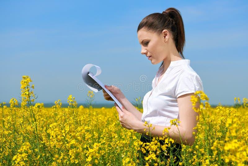 Бизнес-леди в взгляде поля цветка внешнем на доске сзажимом для бумаги Маленькая девочка в желтом поле рапса Красивый ландшафт ве стоковое фото