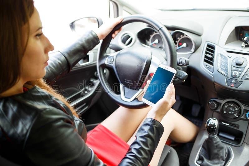 Бизнес-леди в красном платье сидя в автомобиле стоковое изображение
