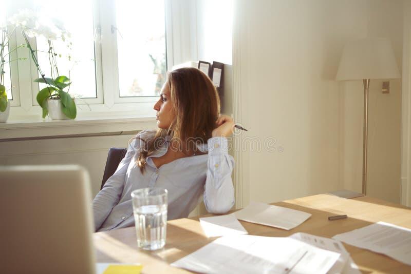 Бизнес-леди в домашнем офисе смотря прочь думающ стоковые изображения rf