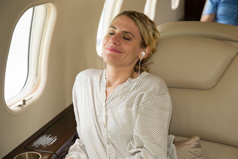 Бизнес-леди в реактивном самолете авиации общего назначения ослабляя и слушая к musi стоковые фотографии rf