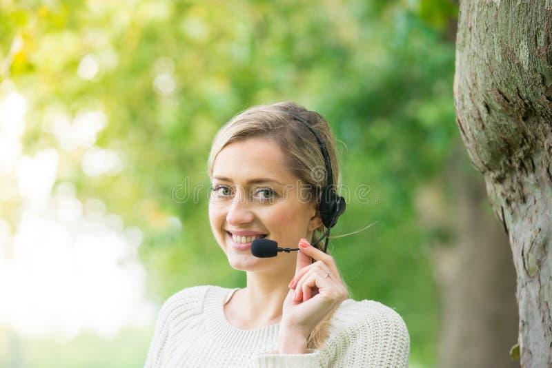Бизнес-леди говоря используя ее шлемофон в парке стоковые фотографии rf