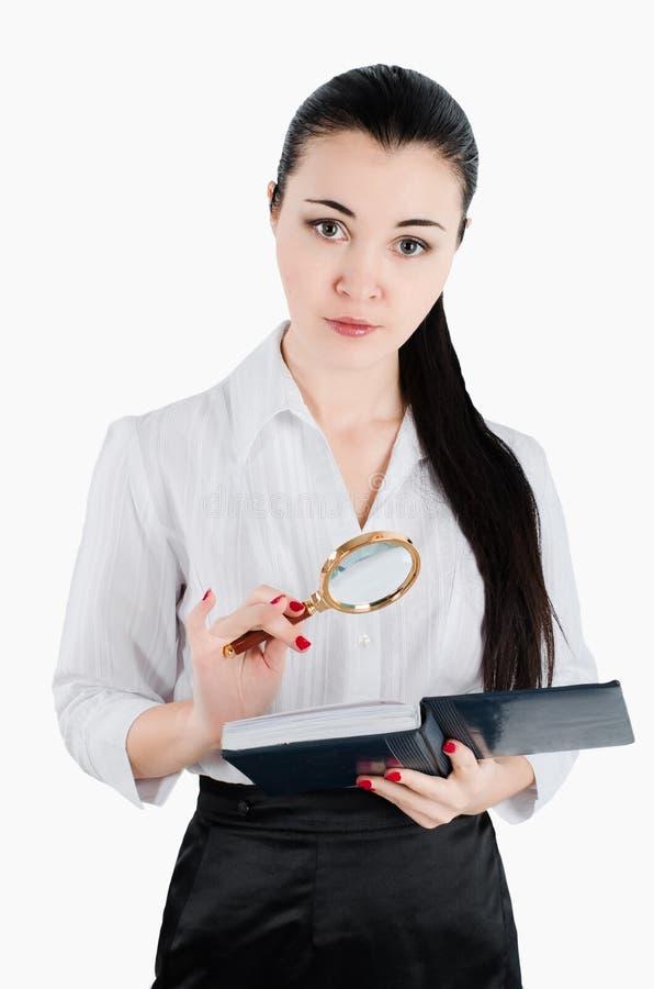 Бизнес-леди держа лупу и книгу Белый isol стоковое изображение