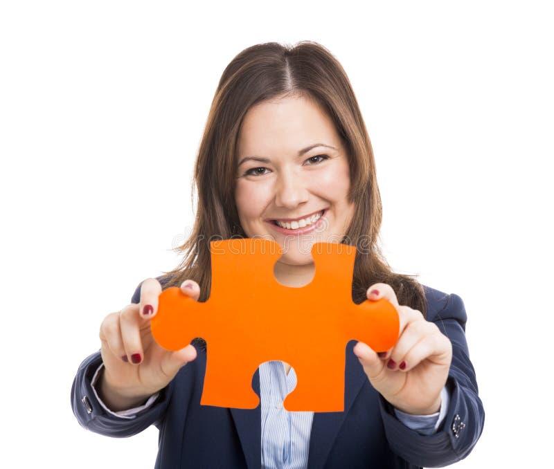 Бизнес-леди держа часть головоломки стоковая фотография