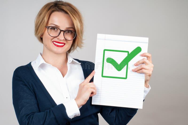 Бизнес-леди держа чистый лист бумаги с проверкой стоковое фото rf