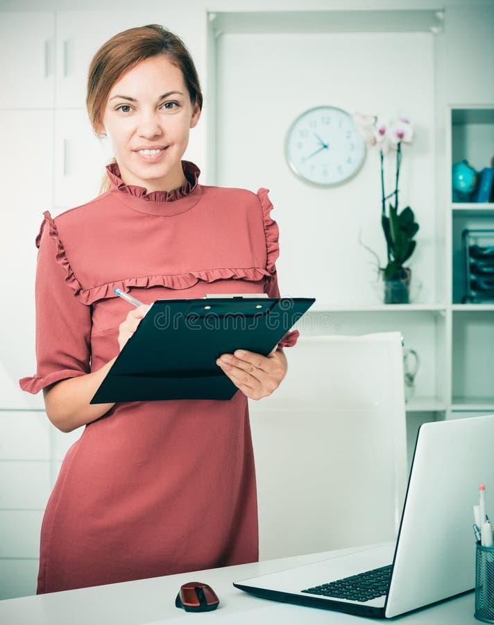 Бизнес-леди имея доску сзажимом для бумаги с документом в руках стоковое изображение