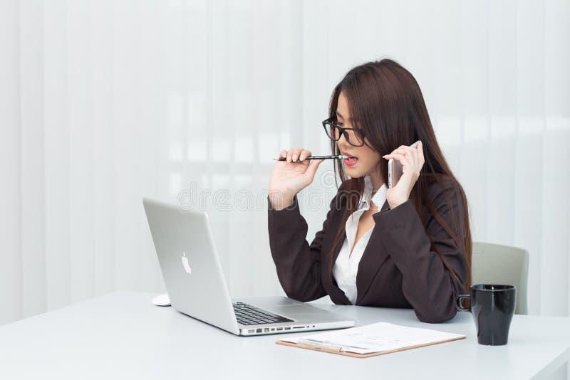 Бизнес-леди используя компьтер-книжку на офисе стоковое изображение