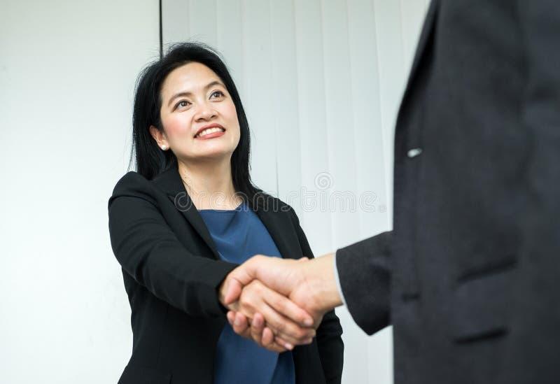 Бизнес-леди и бизнесмен улыбки тряся руку в офисе, PA стоковые фото