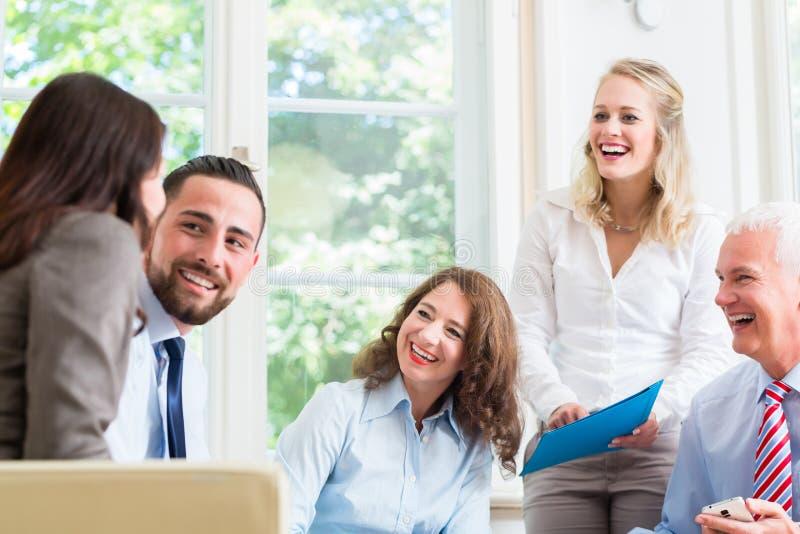 Бизнес-леди и люди в офисе имея представление стоковые изображения