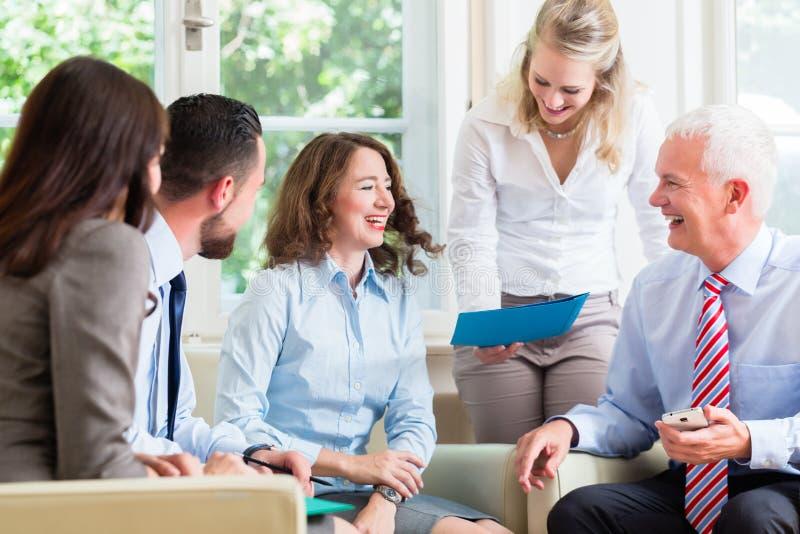 Бизнес-леди и люди в офисе имея представление стоковое изображение rf