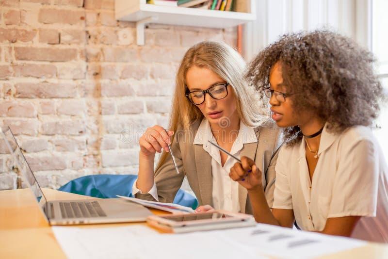 Бизнес-леди на столе офиса работая совместно на компьтер-книжке, концепции сыгранности стоковые изображения