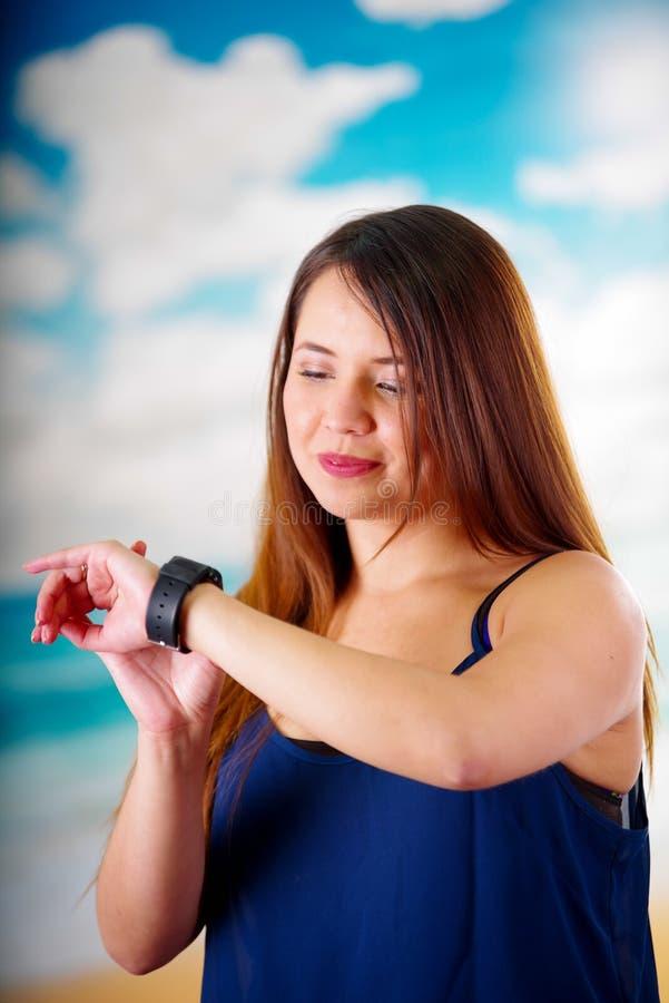 Бизнес-леди нося в ее запястье руки умный вахту с управлением голоса в предпосылке солнечного дня стоковые изображения rf
