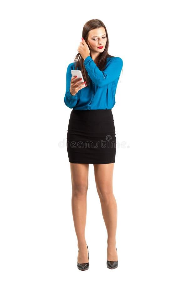 Бизнес-леди проверяя ее волосы путем смотреть на ее отражении или фото мобильного телефона стоковое изображение