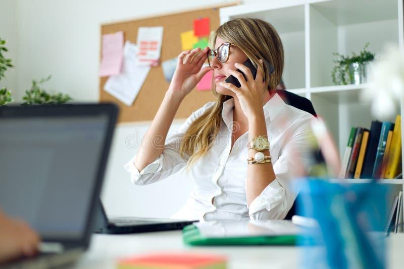 Бизнес-леди работая с мобильным телефоном в ее офисе стоковые фотографии rf