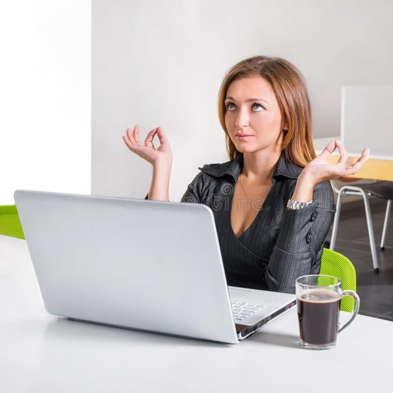 Бизнес-леди размышляя около компьтер-книжки Расслабленный работник офиса делая раздумье йоги во время перерыва на чашку кофе Офис стоковое фото