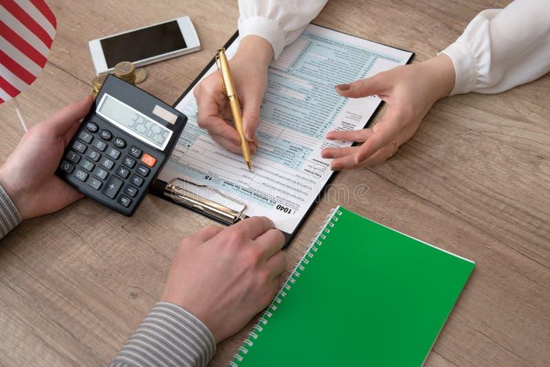 Бизнес-леди рассматривает налоговую форму 1040 стоковая фотография rf