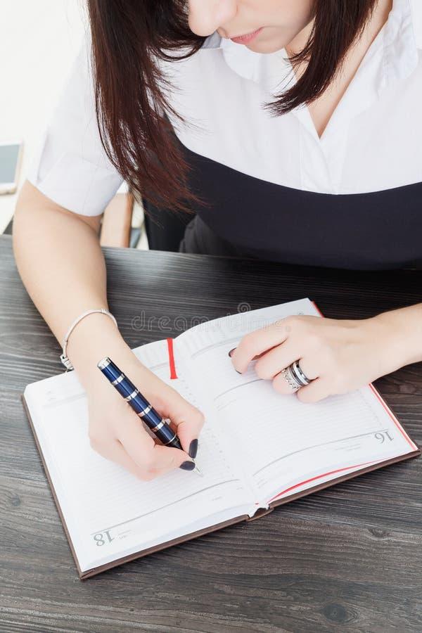 Бизнес-леди сидя на таблице и пишет текст в тетради стоковые изображения rf