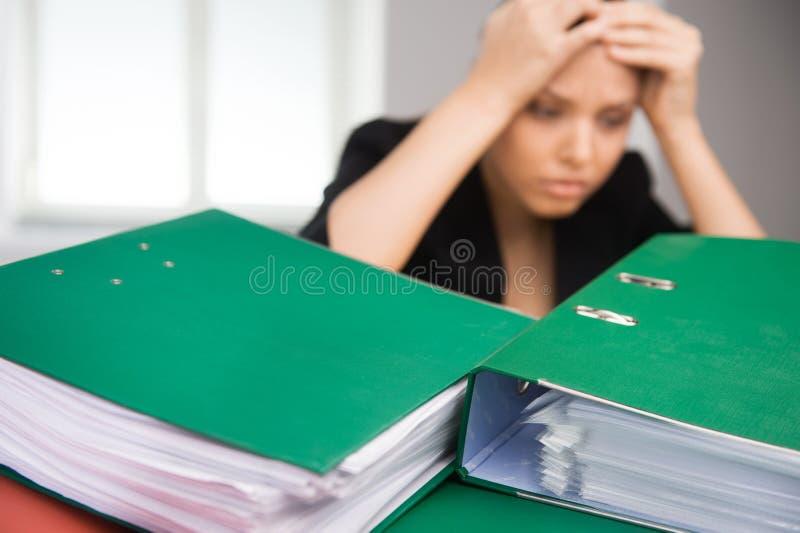 Бизнес-леди сидя на таблице покрытой с папками стоковые изображения rf