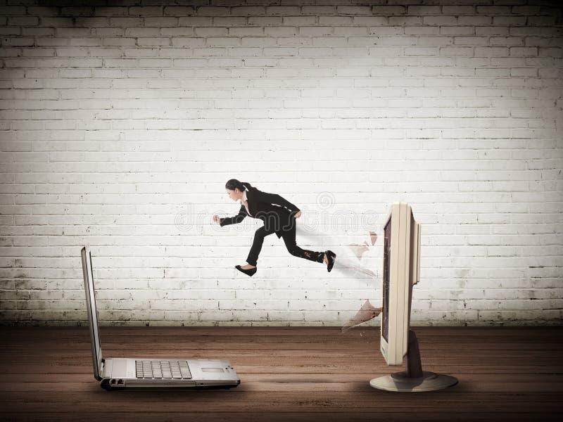 Бизнес-леди скача от настольного компьютера к компьтер-книжке стоковые изображения rf