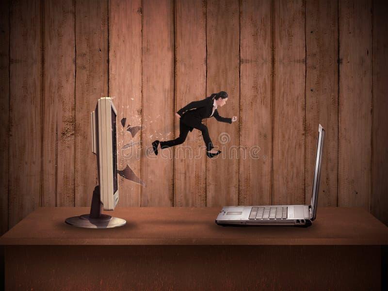 Бизнес-леди скача от настольного компьютера к компьтер-книжке стоковое фото