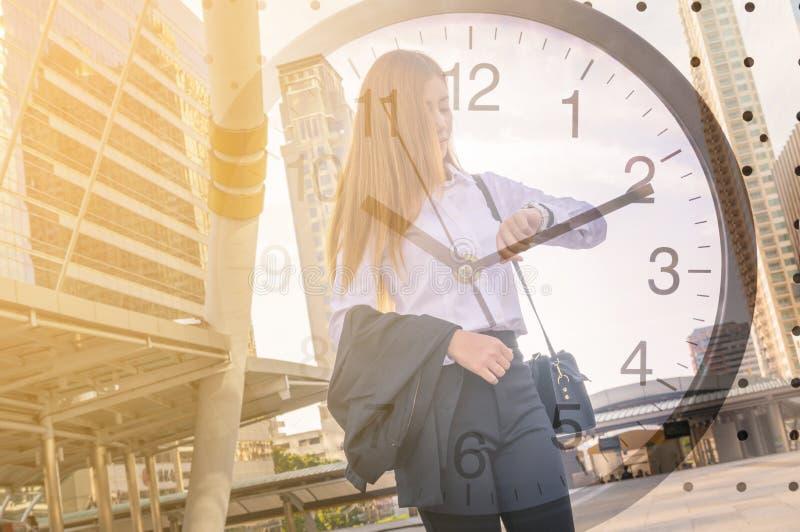 Бизнес-леди смотря вахту в современном городе стоковые изображения