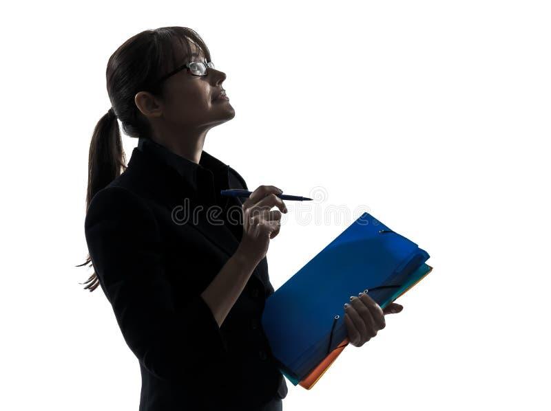 Бизнес-леди смотря вверх держащ силуэт файлов папок стоковое изображение