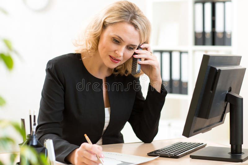 Бизнес-леди среднего возраста говоря на мобильном телефоне в офисе женщина портрета дела ся стоковое фото rf