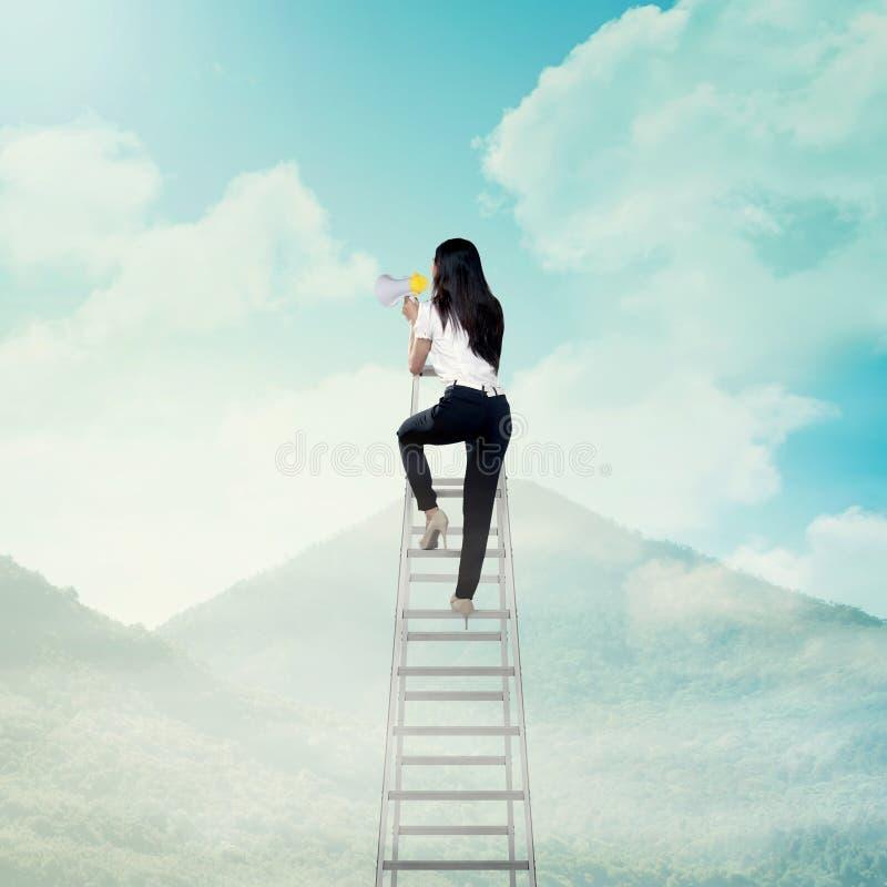 Бизнес-леди стоя на лестнице высокой и окрике с мегафоном стоковые изображения